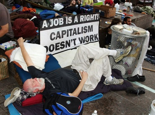 A man at the protest event Occupy Wall Street critiquing Capitalism in the context of the right to have a job.