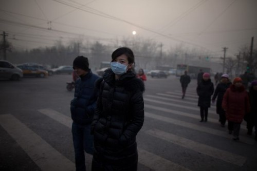 A woman wearing a mask crosses a road during severe pollution in Beijing on January 12, 2013. Air quality data released via the US embassy twitter feed recorded air quality index levels so hazardous that they were classed as 'Beyond Index'. By 4pm the particle matter (PM) 2.5 figure was 728 on a scale that stops at 500 at which point the US embassy website advises against all outdoor activity. AFP PHOTO / Ed Jones