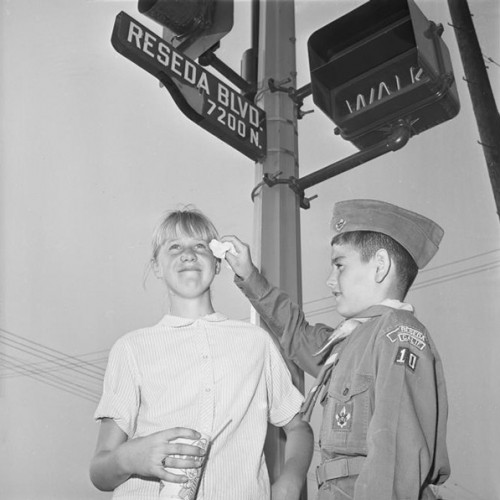 Boy scout Jeffrey La France wipes tears from the eyes of Nancy Rayder during a smog alert in Reseda on October 7, 1965. Courtesy of UCLA Library Special Collections.