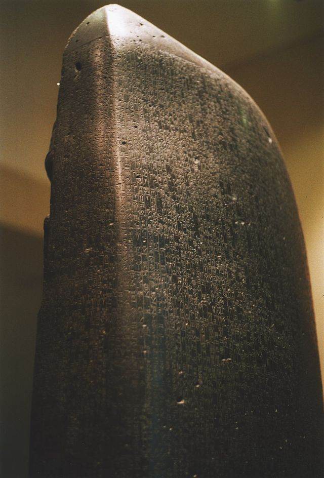 A nearly complete example of the Code of Hammurabi survives today, on a diorite stele in the shape of a huge index finger (7.4 ft) tall. The Code is inscribed in the Akkadian language, using cuneiform script carved into the stele. It is currently on display in the Louvre in Paris.